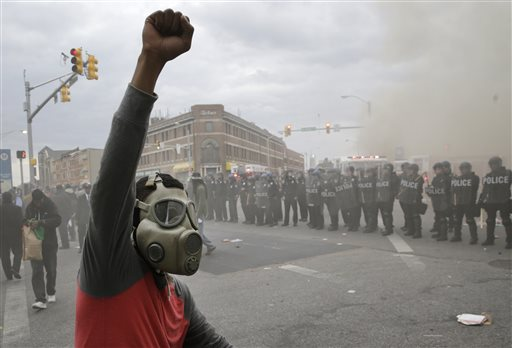 A demonstrator raises his fist as police stand in formation as a store burns, Monday, April 27, 2015, during unrest following the funeral of Freddie Gray in Baltimore. (AP Photo/Patrick Semansky)