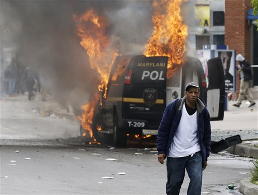 A man walks past a burning police vehicle, Monday, April 27, 2015, during unrest following the funeral of Freddie Gray in Baltimore. Gray died from spinal injuries about a week after he was arrested and transported in a Baltimore Police Department...