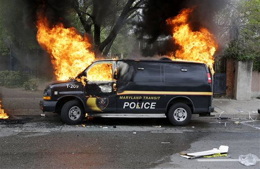 A police vehicle burns, Monday, April 27, 2015, during unrest following the funeral of Freddie Gray in Baltimore. Gray died from spinal injuries about a week after he was arrested and transported in a Baltimore Police Department van. (AP...