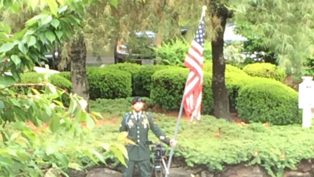 Soldier holding flag at Wingate in Wilbraham