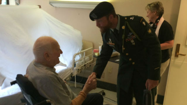 Soldier holding flag shaking hands