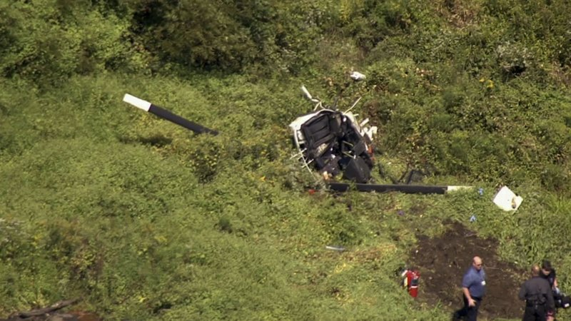 In this image from video provided by NBC10 Philadelphia, first responders are positioned near the wreckage of a helicopter in Lumberton, N.J., Friday, Sept. 8, 2017. The Federal Aviation Administration says the helicopter crashed into a wooded...