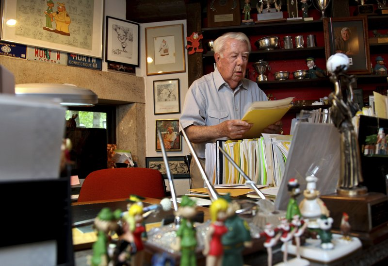 FILE - In this Aug. 16, 2010 file photo, Mort Walker, the artist and author of the Beetle Bailey comic strip, looks over notes and documents in his studio in Stamford, Conn. On Saturday, Jan. 27, 2018, a family member said the comic strip artist...