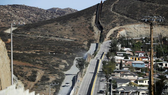 FILE - In this Nov. 9, 2016 file photo, a Border Patrol vehicle drives by the border fence in Tecate, Calif., left, along the metal barrier that lines the border, seen from Tecate, Mexico. The Trump administration has proposed spending $18 billion...