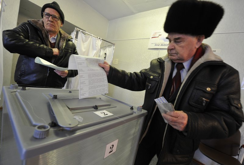 Two men cast their ballots at a polling station in Yelizovo, about 30 kilometers ( 19 miles) north-east from Petropavlovsk-Kamchatsky, capital of Kamchatka Peninsula region, Russian Far East, Russia, on Sunday, March. 18, 2018. Polls have opened...